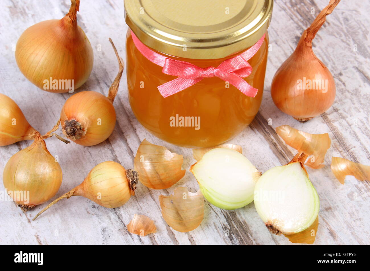 Fresh organic honey in glass jar and onions on old rustic wooden background, healthy nutrition, strengthening immunity - Stock Image