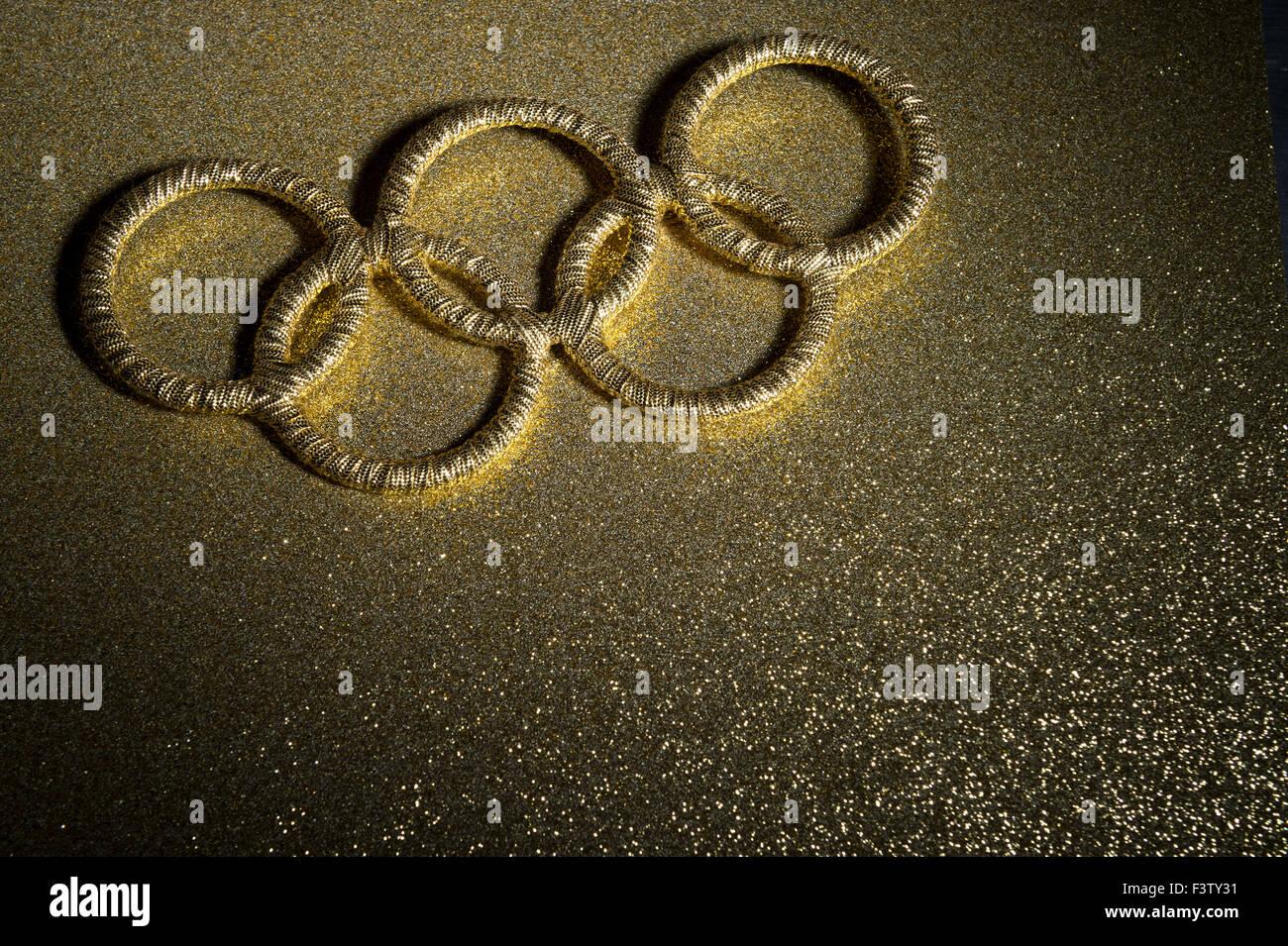 RIO DE JANEIRO, BRAZIL - FEBRUARY 3, 2015: Gold Olympic rings symbol sits spotlit on shiny golden background. - Stock Image