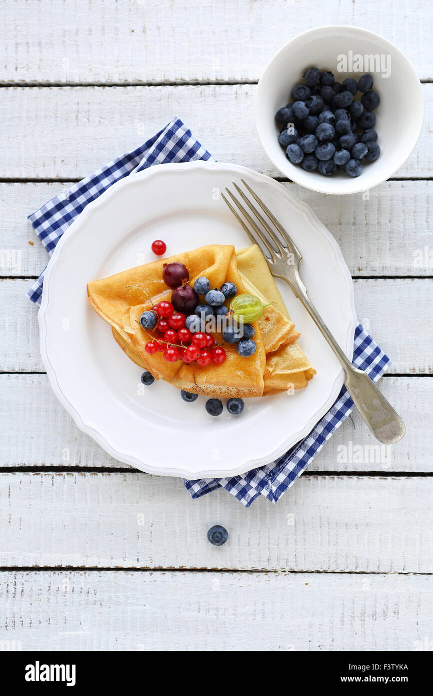 pancakes for breakfast with berries on plate - Stock Image