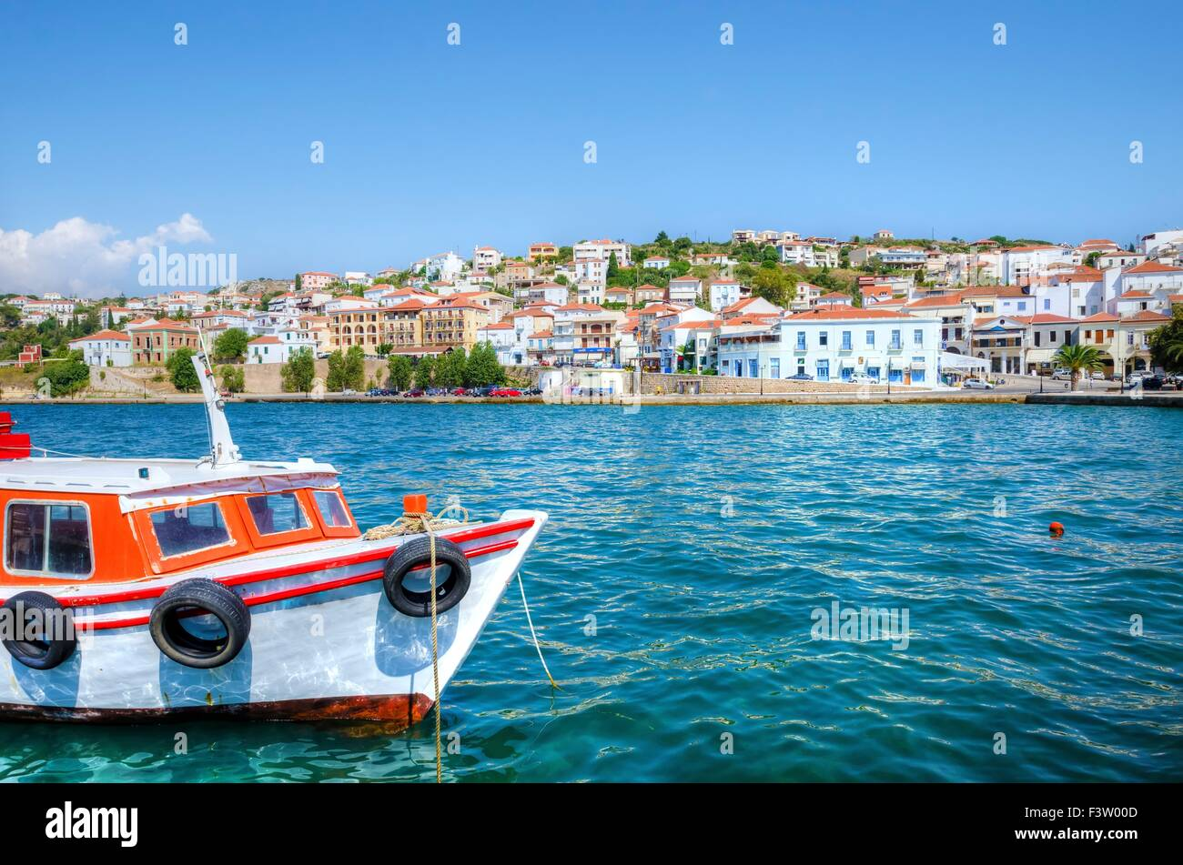 A view of a boat in the port of Pylos, a Greek city in Peloponnese (south Greece) and some local architecture in - Stock Image
