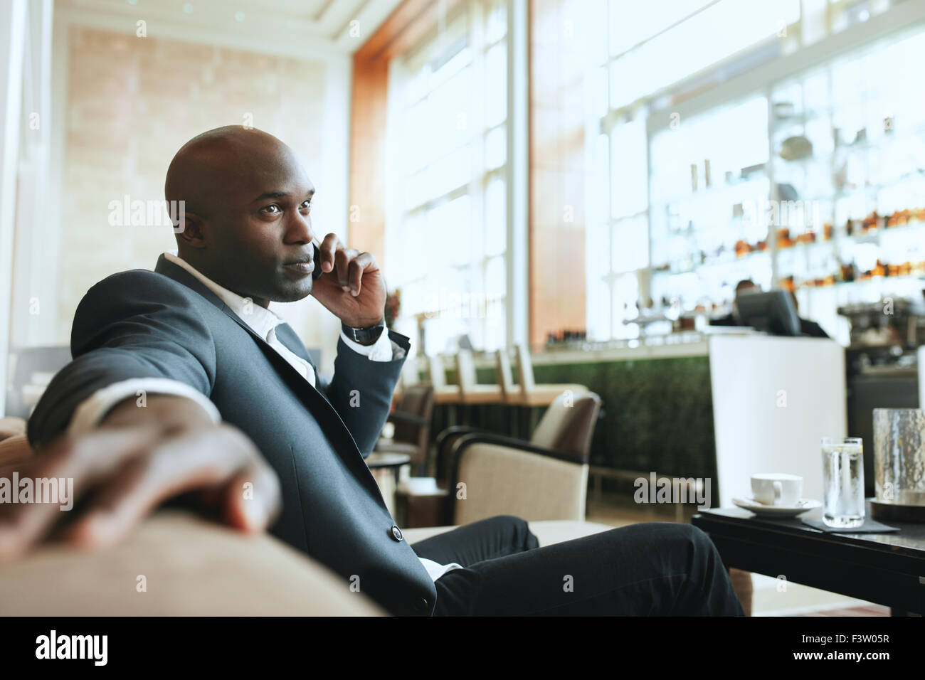African business man talking on mobile phone while waiting in a hotel lobby. Young business executive using cell - Stock Image
