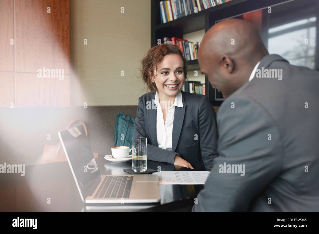 Two business partners sitting in cafe and discussing business plan. Businessman and businesswoman smiling during - Stock Image