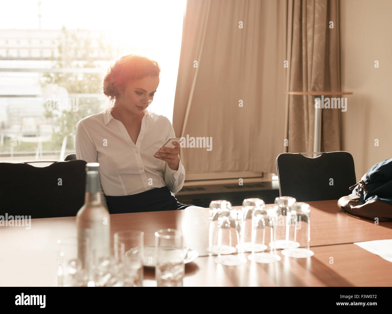 Portrait of young businesswoman sitting in business conference room using mobile phone. Female executive sitting - Stock Image