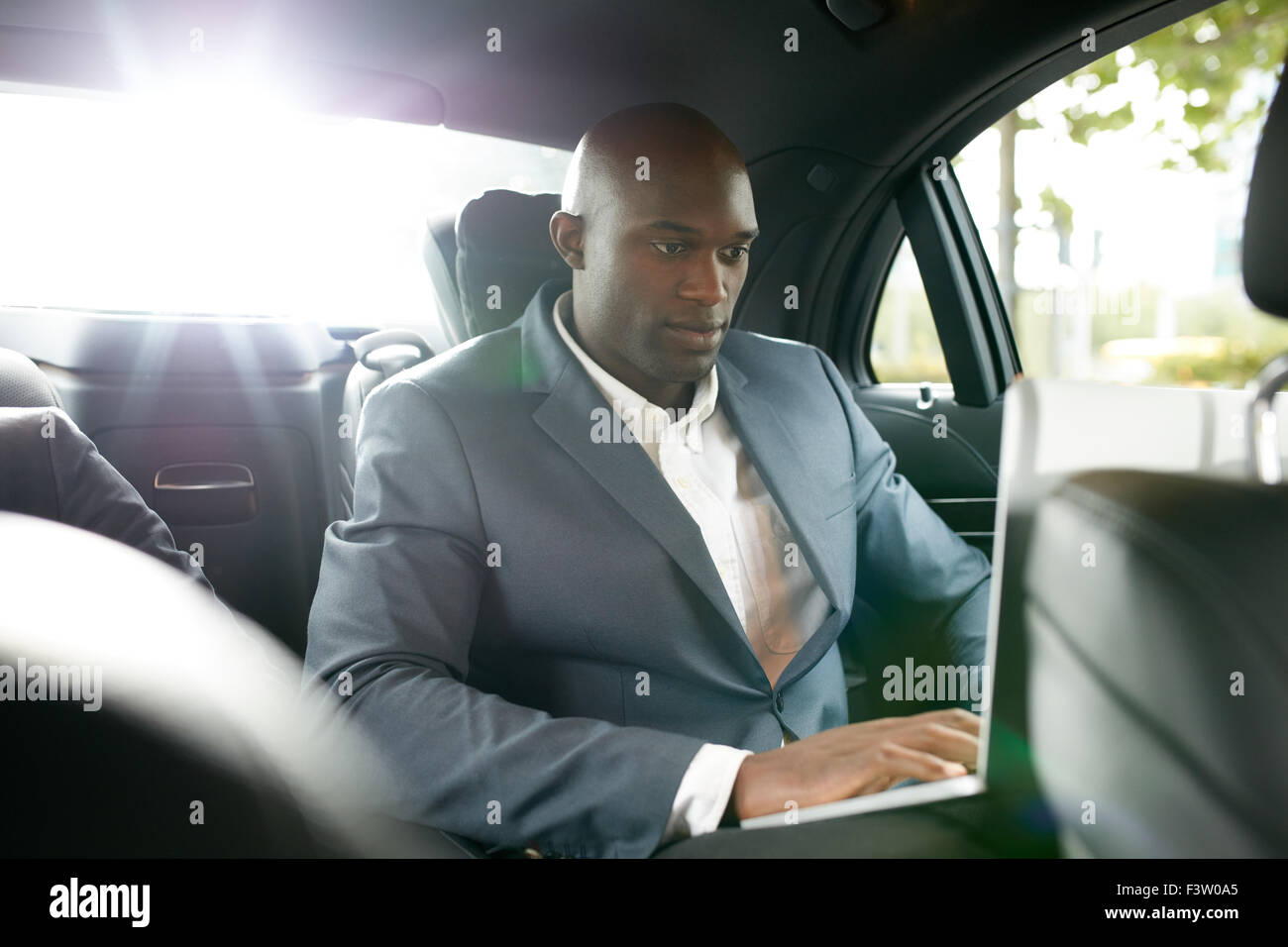 Shot of happy young businessman traveling to work in the luxury car on the back seat and using laptop. African business - Stock Image