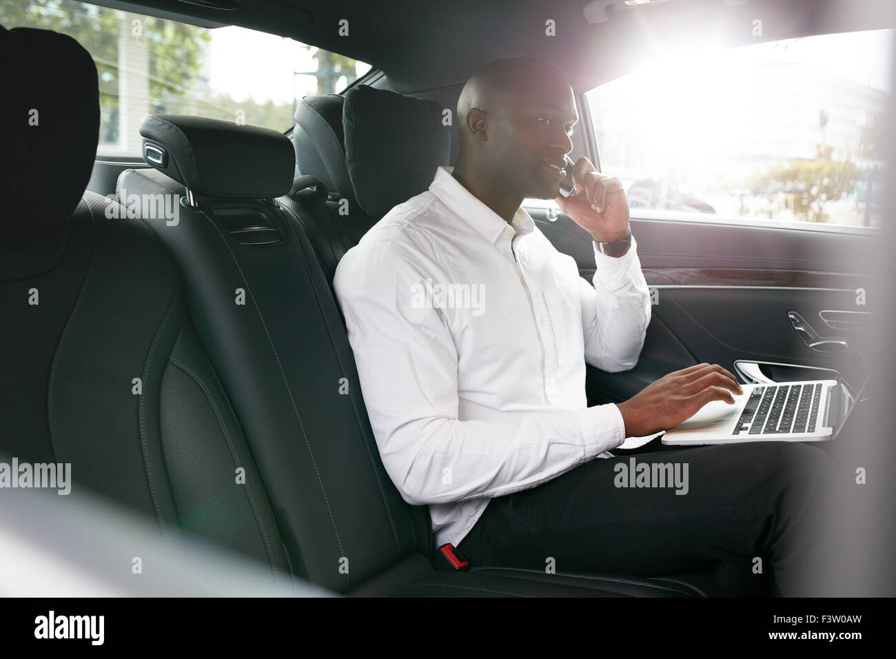 Businessman with laptop receiving a phone call on the backseat of a car. African businessman working during travelling - Stock Image