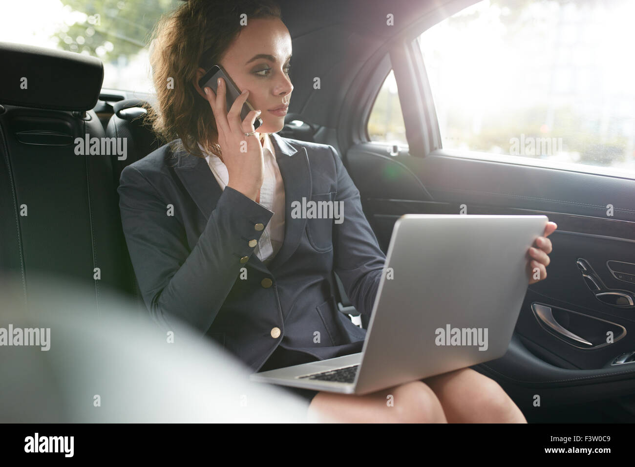 Businesswoman sitting on back seat of car with laptop talking on mobile phone. Female executive travelling to work - Stock Image