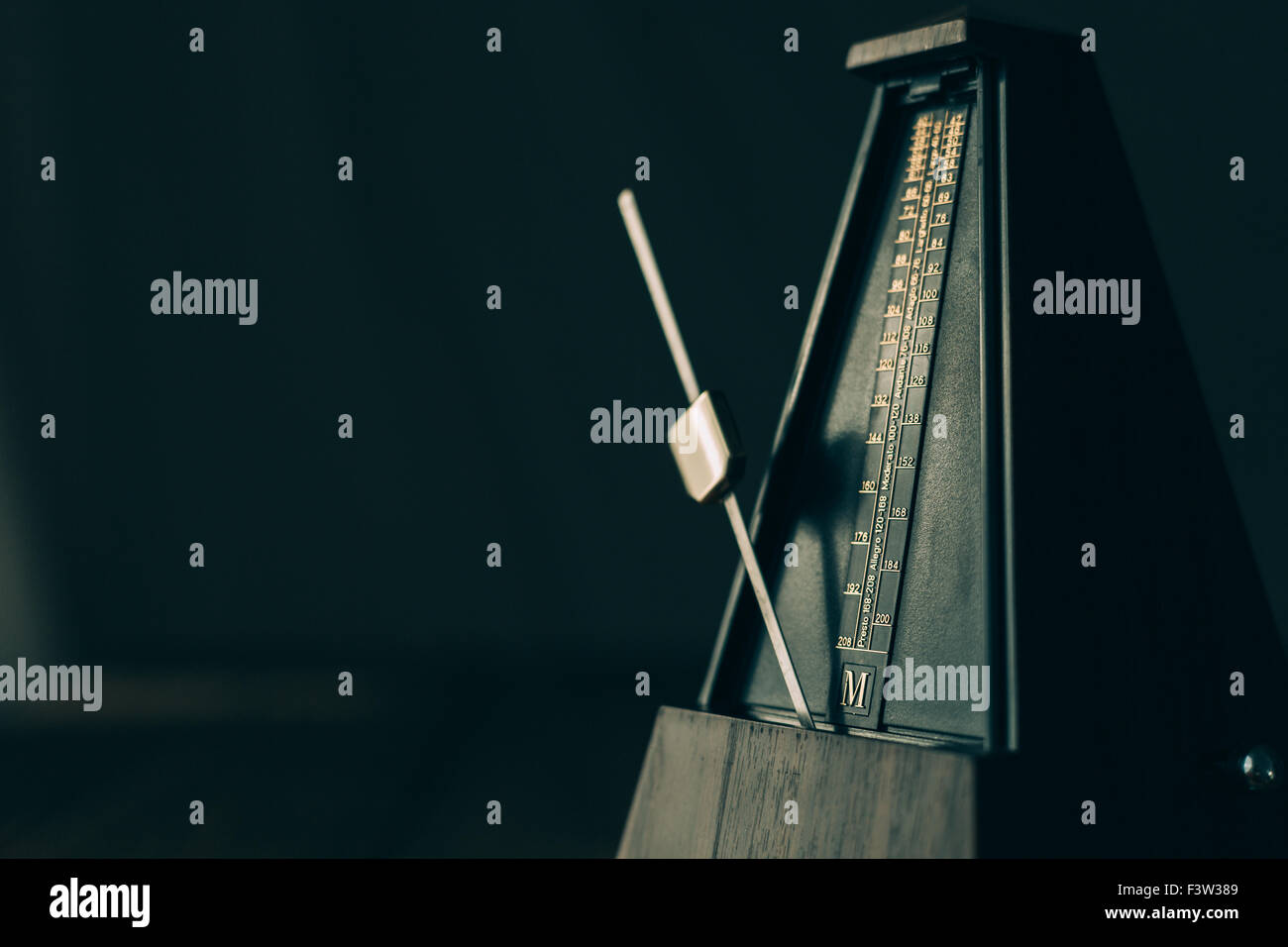 Vintage metronome, on a dark background. - Stock Image