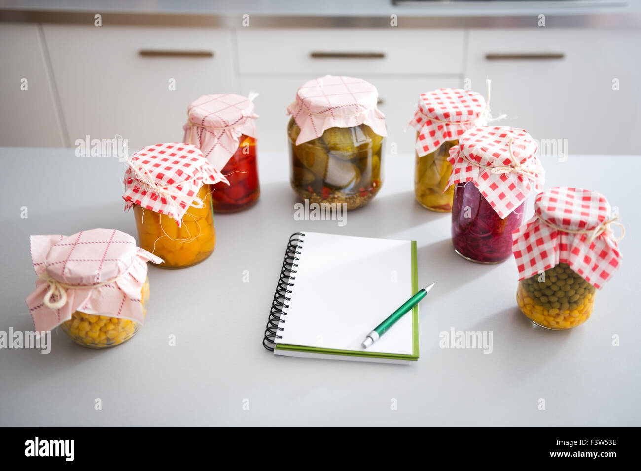 Corn, pumpkin, peppers, dill pickles, beans, red cabbage, and peas have all been preserved in glass jars. - Stock Image