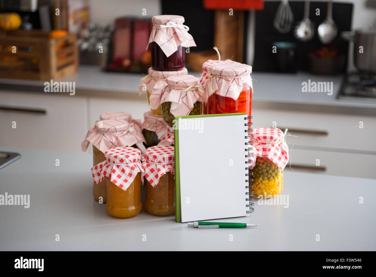 A stack of glass jars filled with preserved vegetables is standing on the kitchen counter. Leaning up against them, - Stock Image