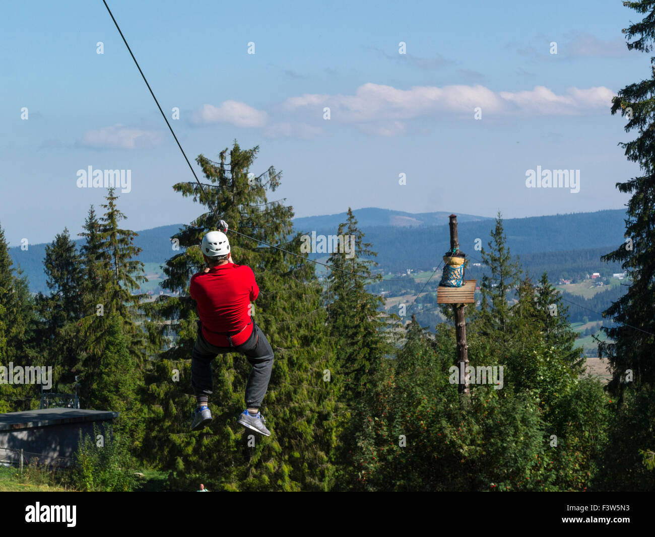 Young man on zipwire of Trollandia Highwire park Gubalowka Hill Zakopane Poland excitement adrenalin rush on lovely - Stock Image