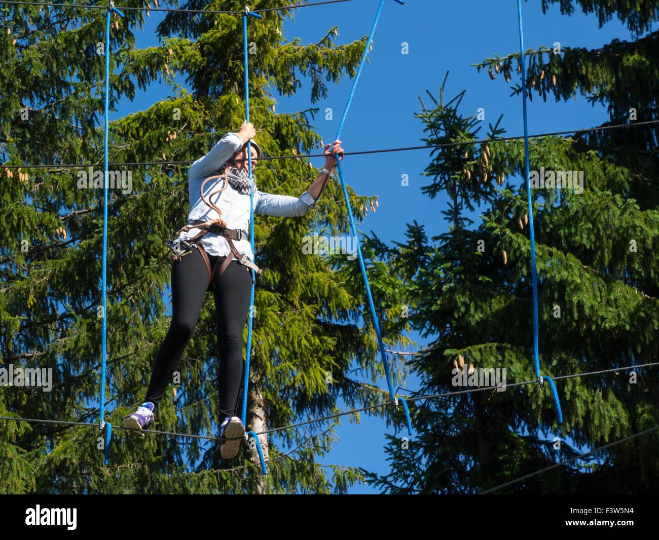Young girl negotiating a rope walkway of  Trollandia Highwire Park Gubalowka Hill Zakopane Poland  excitement adrenalin - Stock Image