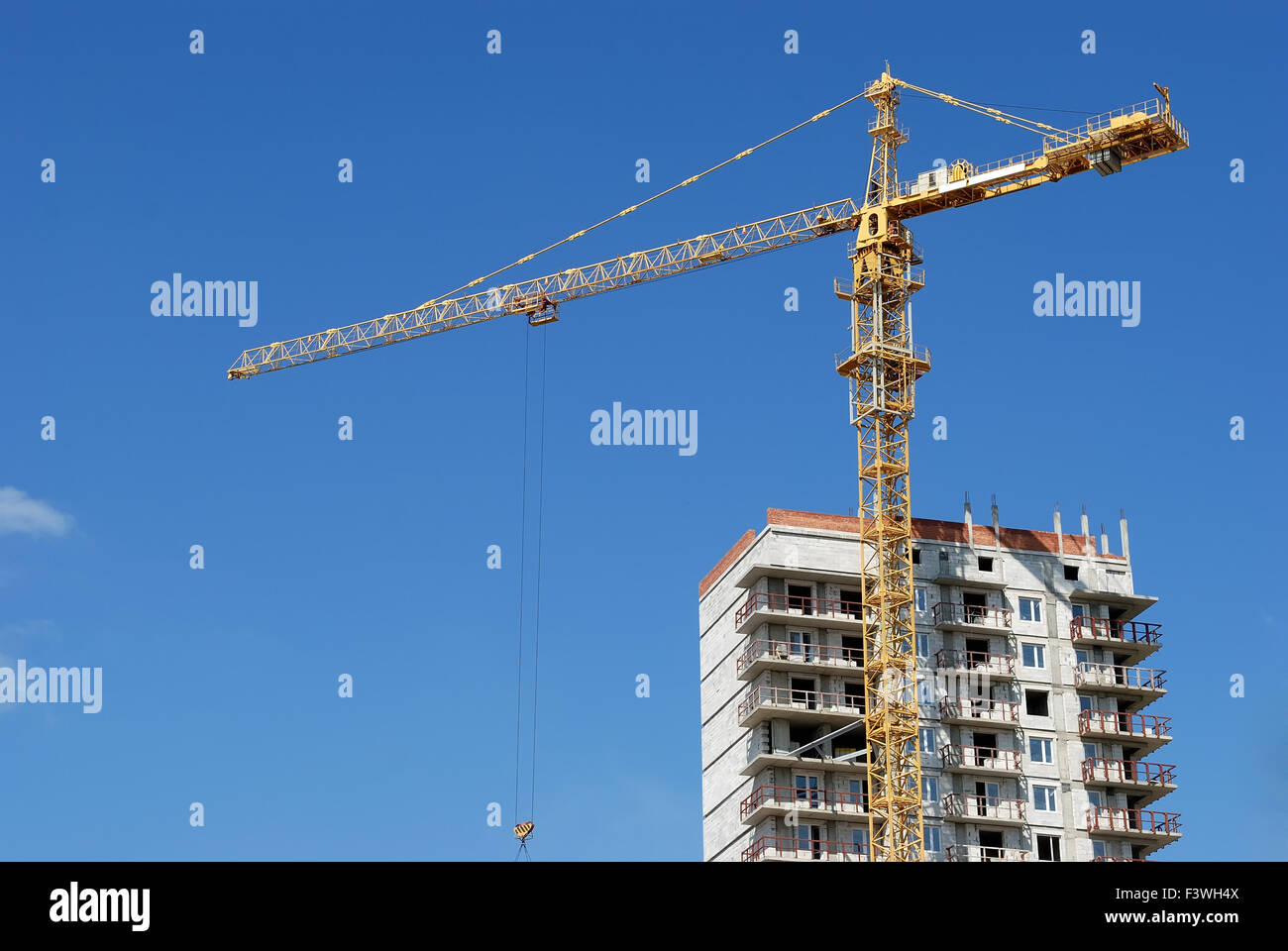 Yellow tower crane at multistory building - Stock Image