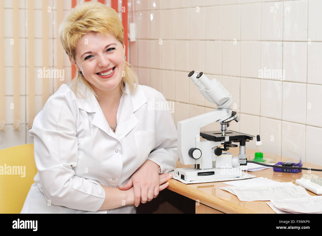 woman medic Scientist and microscope - Stock Image