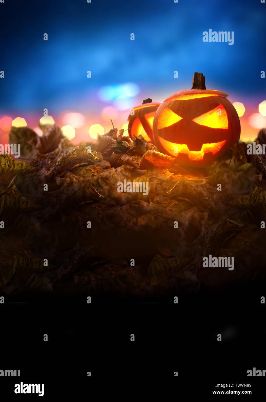 Halloween Night. A Jack O Lantern Pumpkin glowing orange on Halloween evening between autumn leaves. - Stock Image