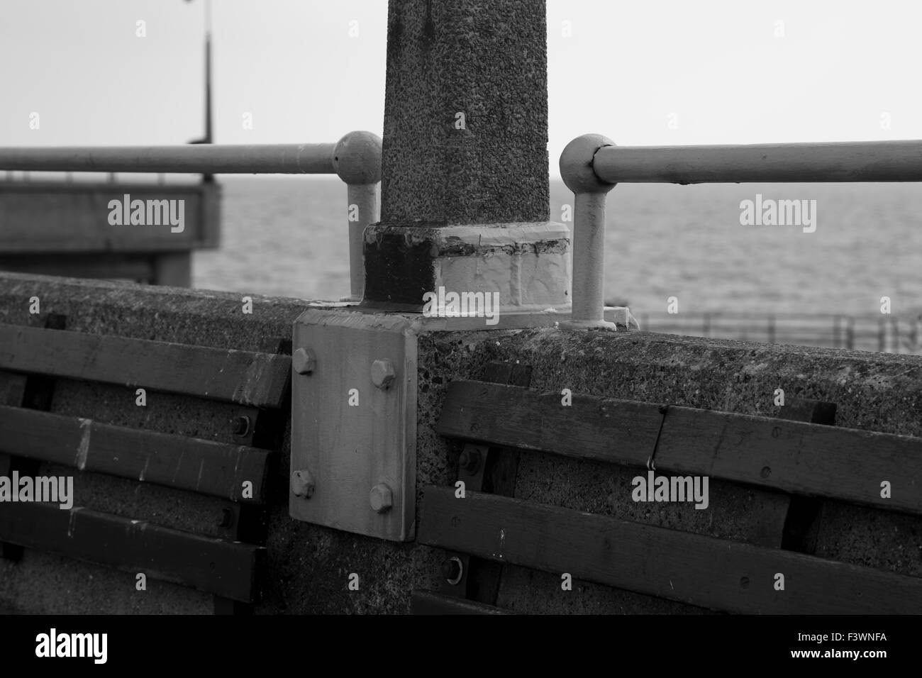 Black and white image of Deal Pier with the english channel in the background, focussing on a metal bracket and - Stock Image