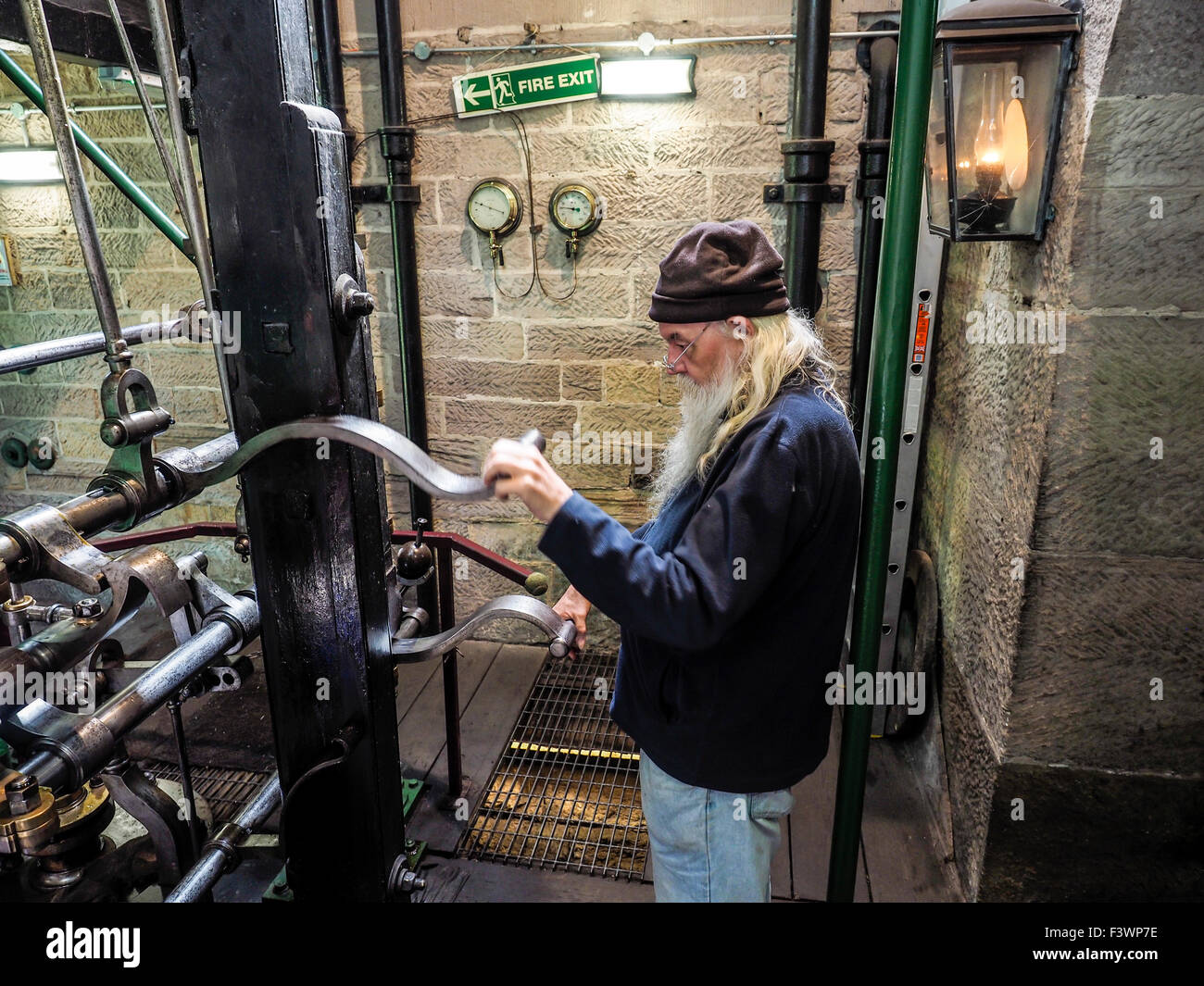 Old man operating equipment Leawood pump house on the Cromford canal in the Peak District Derbyshire England Stock Photo
