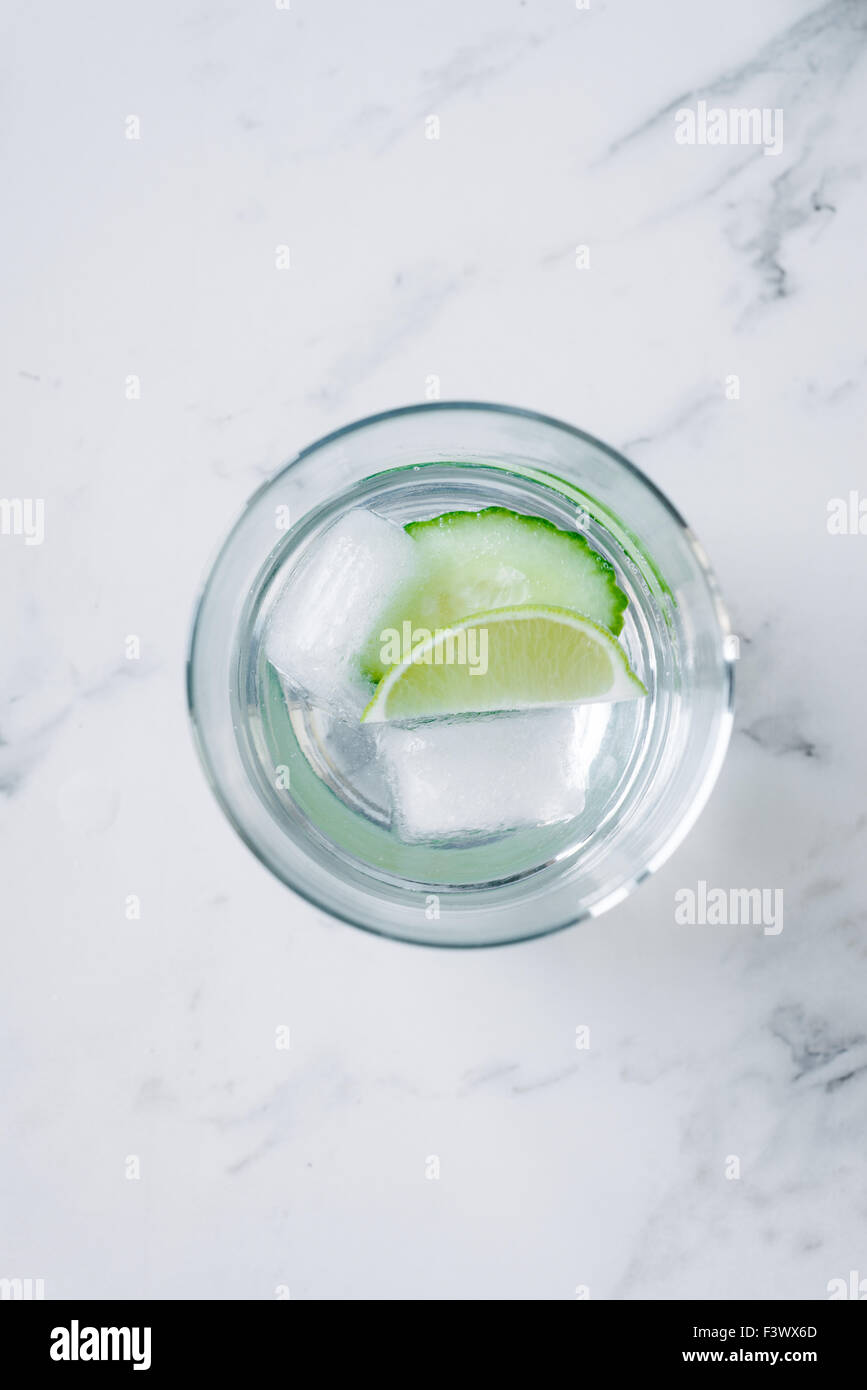 gin and tonic with cucumber, on a marble benchtop - Stock Image