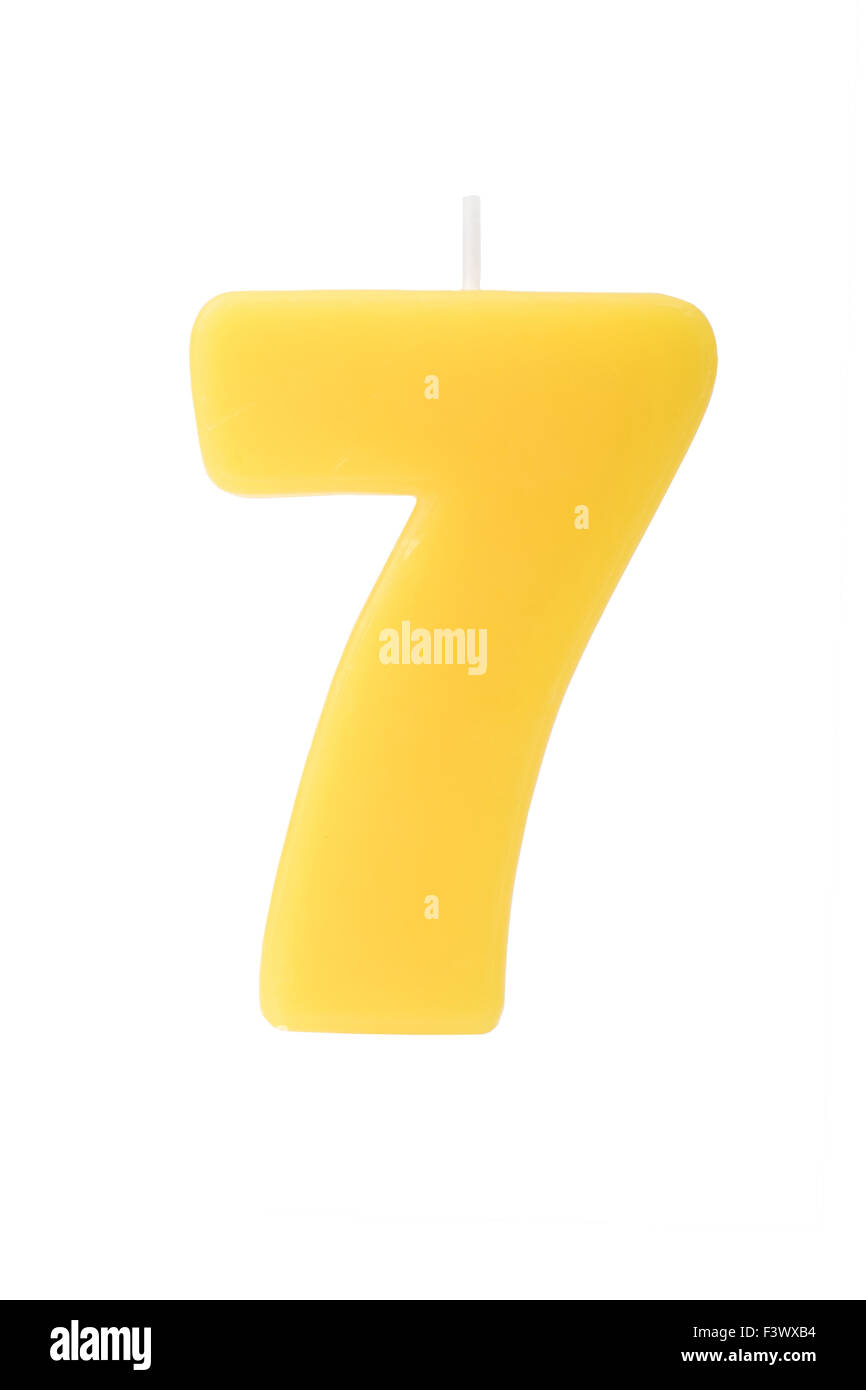 Yelllow birthday candle in the form of the number seven on white background - Stock Image