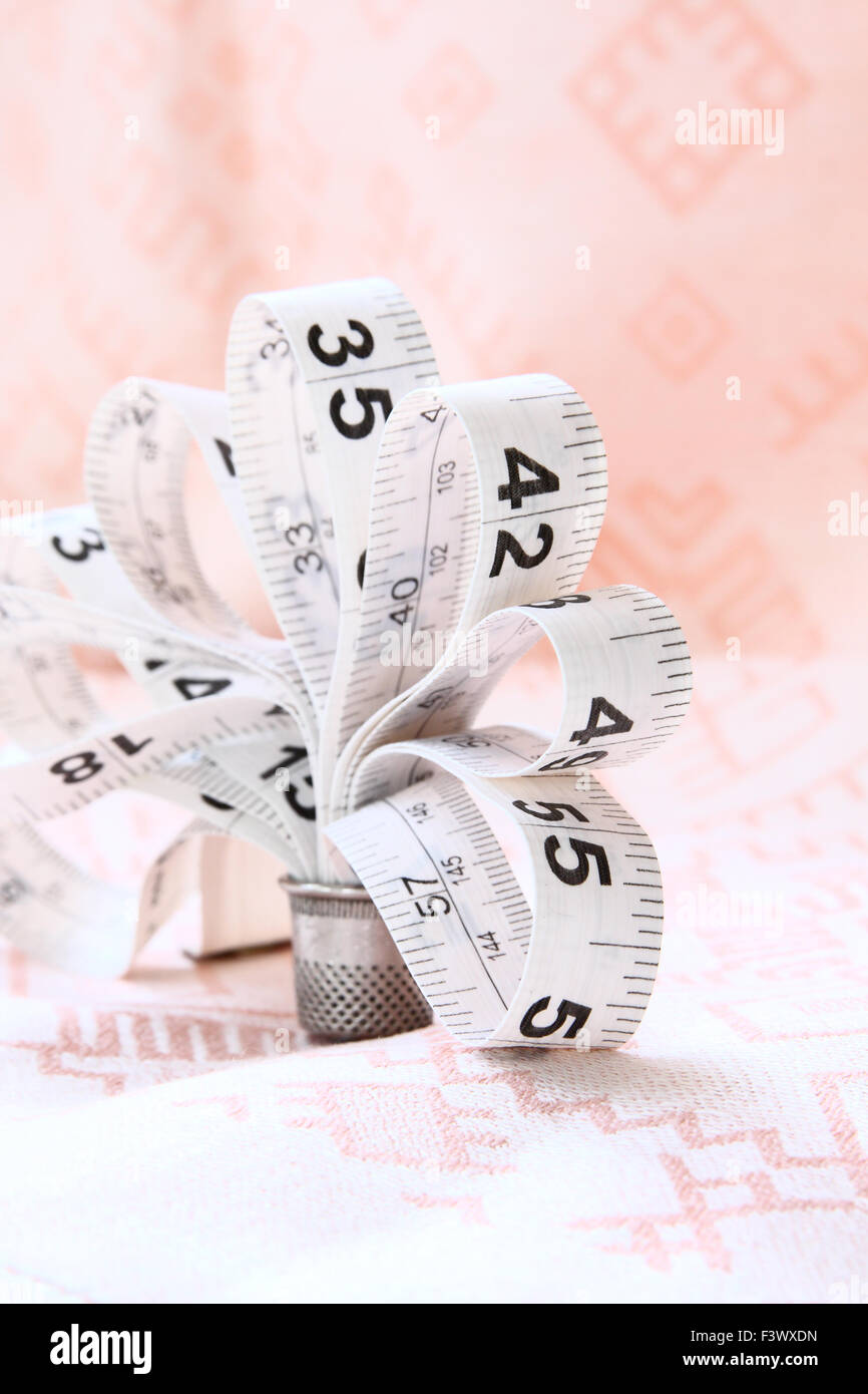 White measuring tape, like a flower - Stock Image