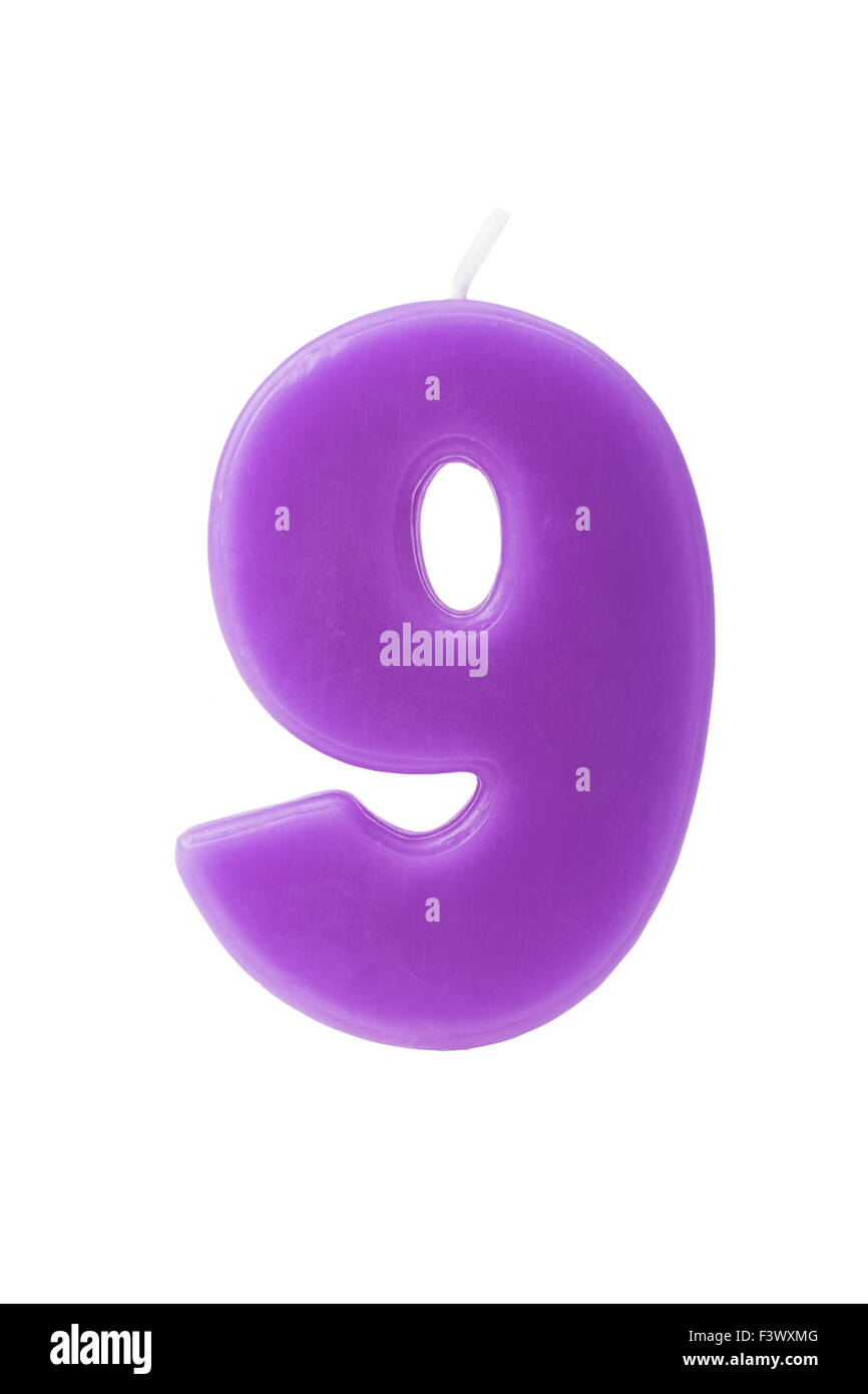 Purple birthday candle in the form of the number nine on white background - Stock Image