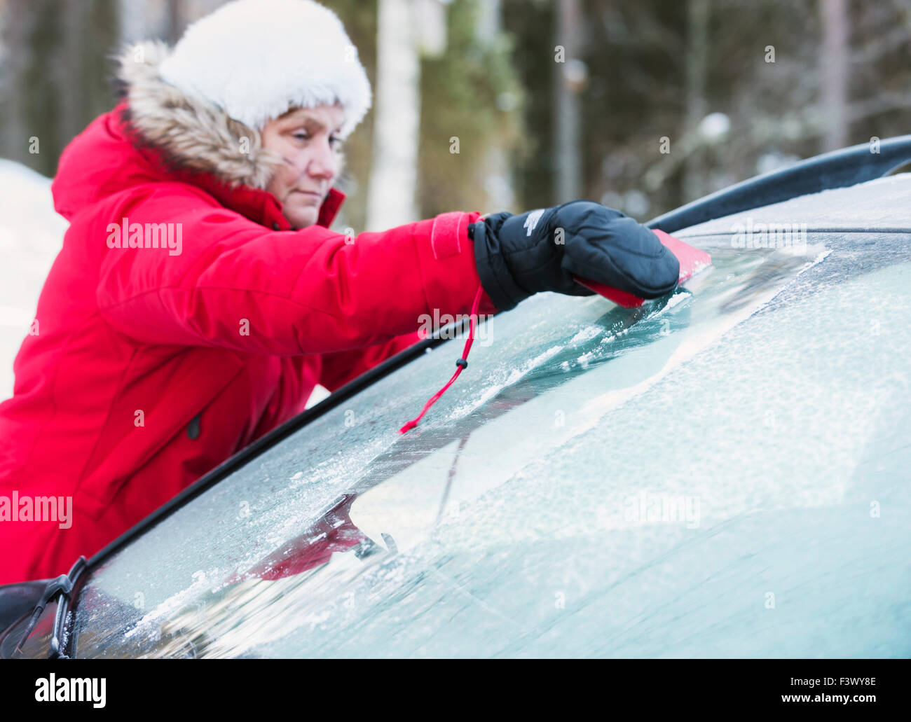 Woman with ice scraper - Stock Image
