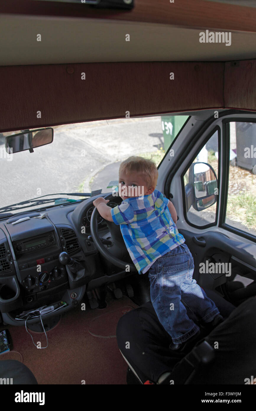 Toddler driving stationary motorhome - Stock Image
