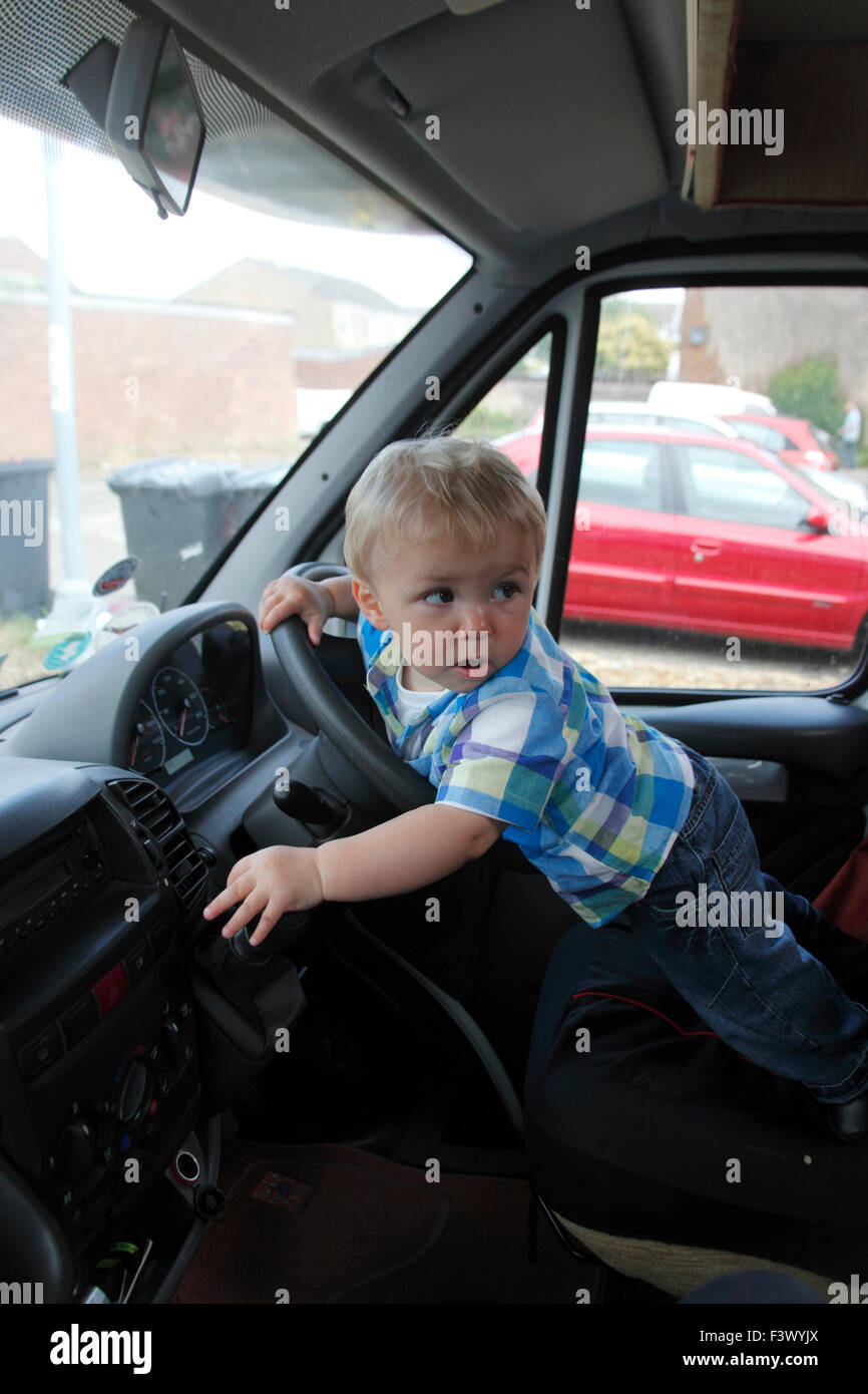 Toddler pretending to drive stationary motorhome - Stock Image
