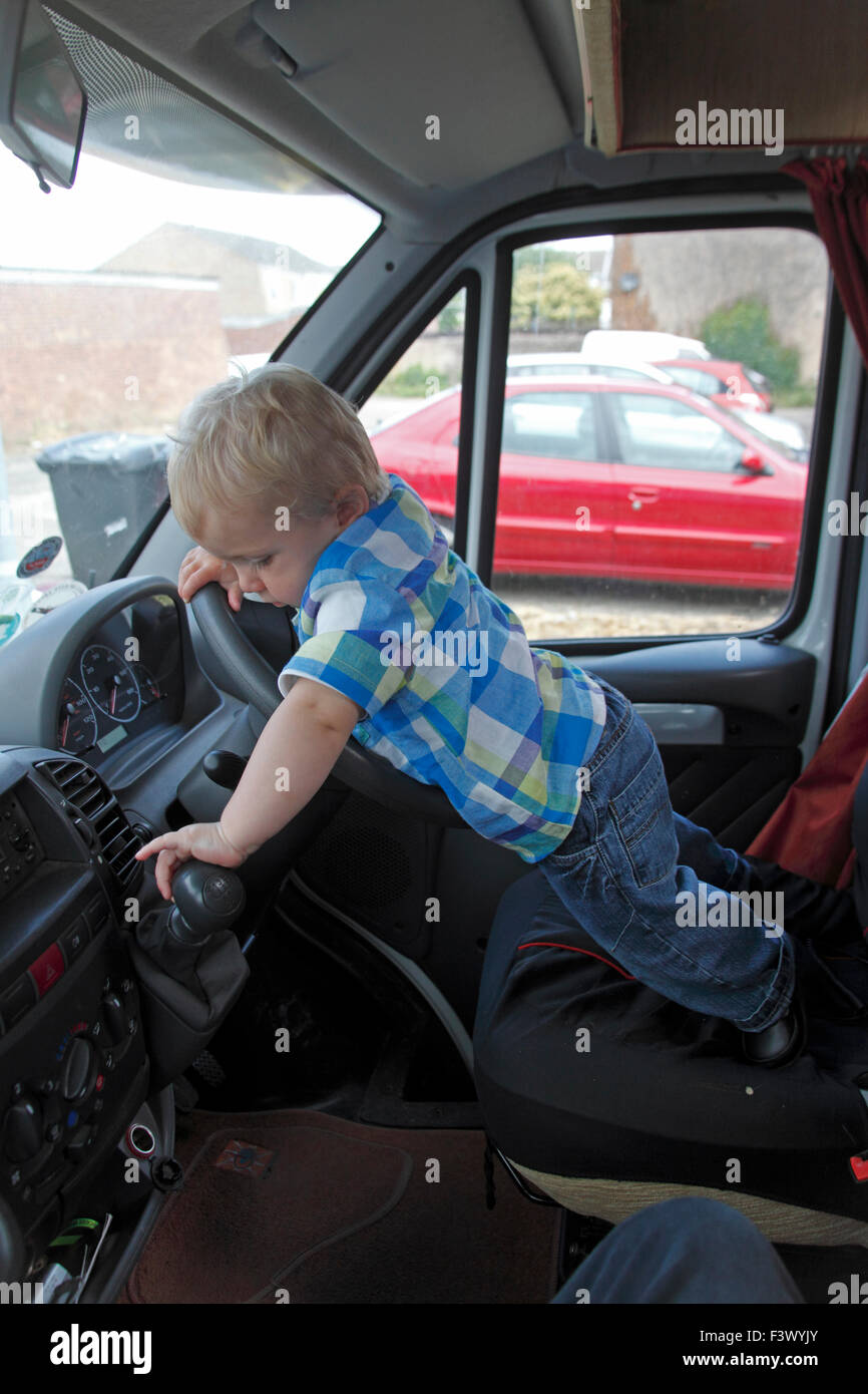 Toddler trying to operete gear lever in stationary motorhome - Stock Image
