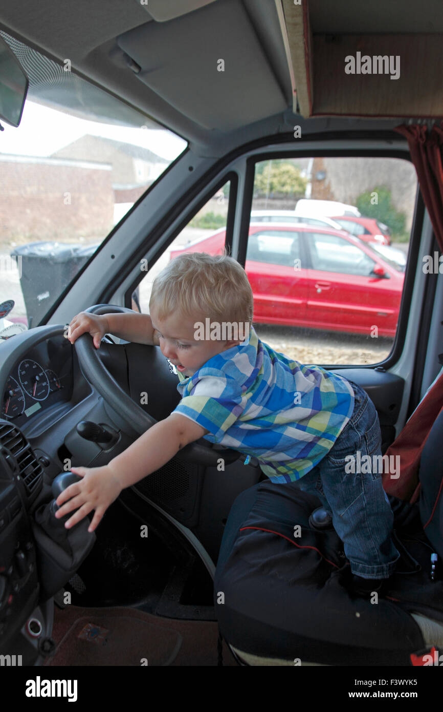 Toddler trying to work gear lever in stationary motorhome - Stock Image
