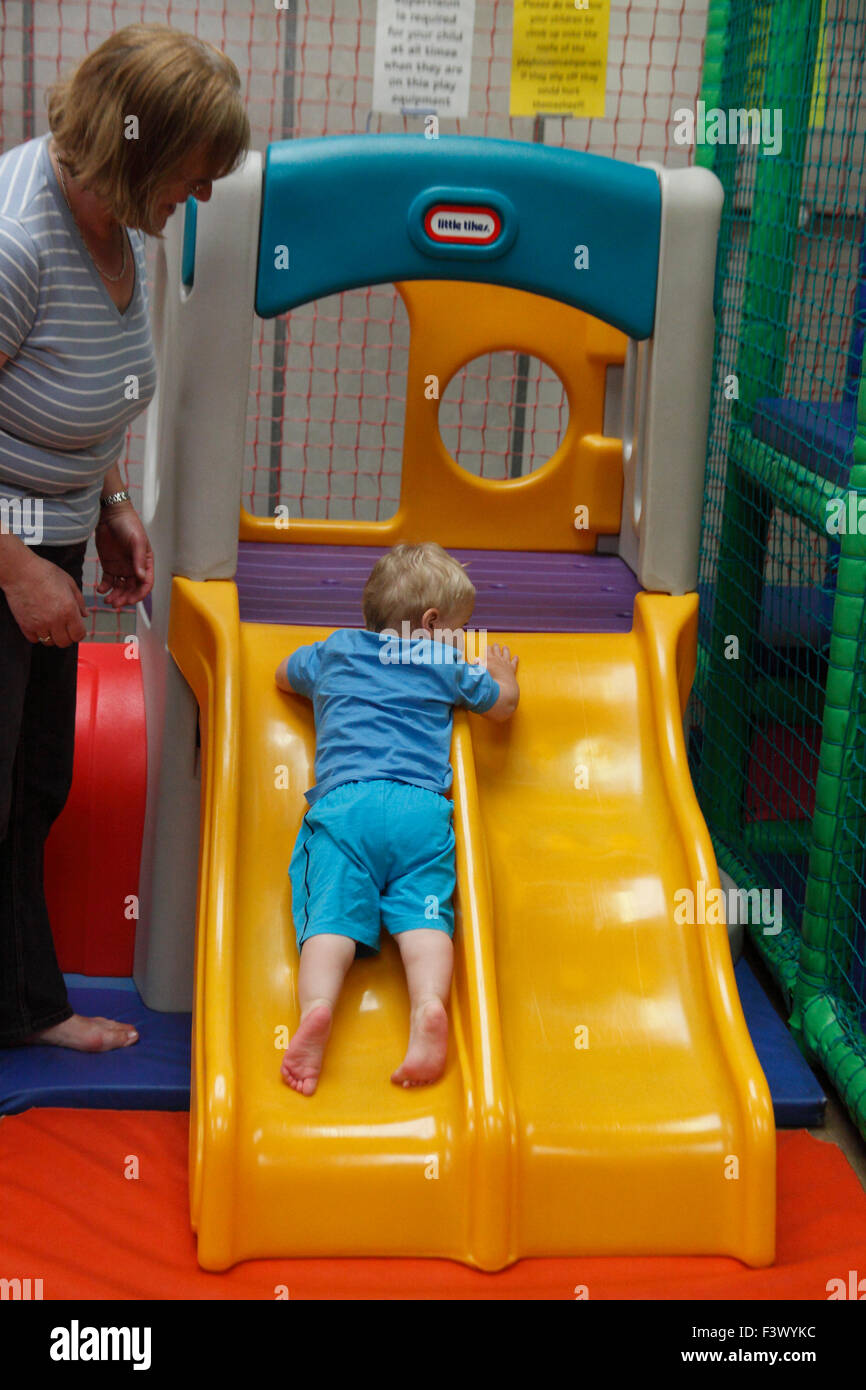 Toddler learning how to use slide under supervision at undercover play area - Stock Image