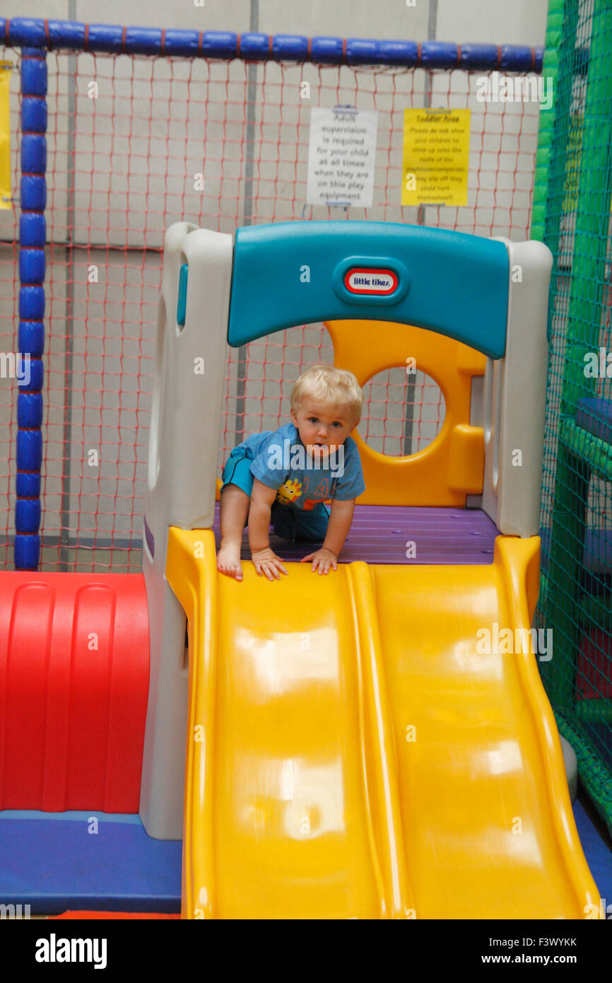 Toddler on top of slide in undercover play area - Stock Image