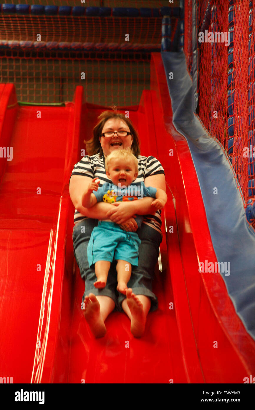 Mother and toddler coming down high slide in playbarn - Stock Image