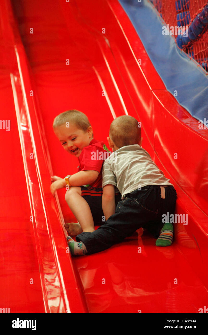 Young boys messing about on slide in playbarn - Stock Image