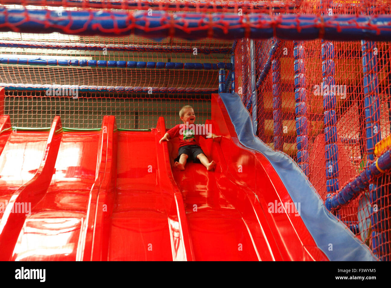 Young boy coming down slide in playbarn - Stock Image