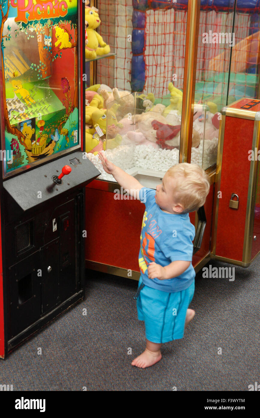 Toddler with arcade machine in playbarn - Stock Image