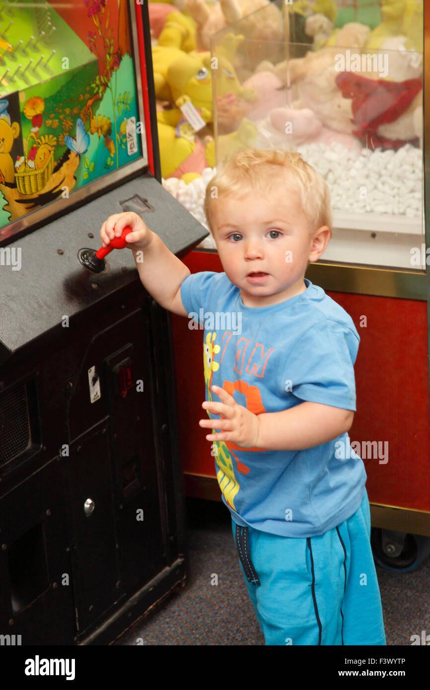 Toddler playing arcade machine in playbarn - Stock Image