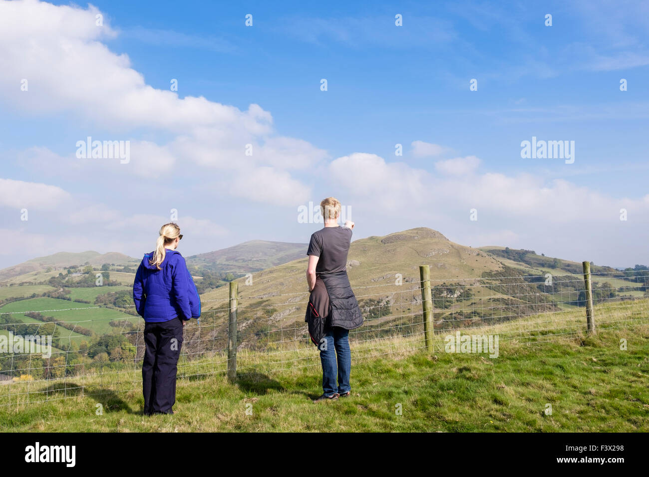 Two walkers looking at a view to Roundton fort from Todleth Hill, Churchstoke or Church Stoke (Yr Ystog), Montgomery, Stock Photo