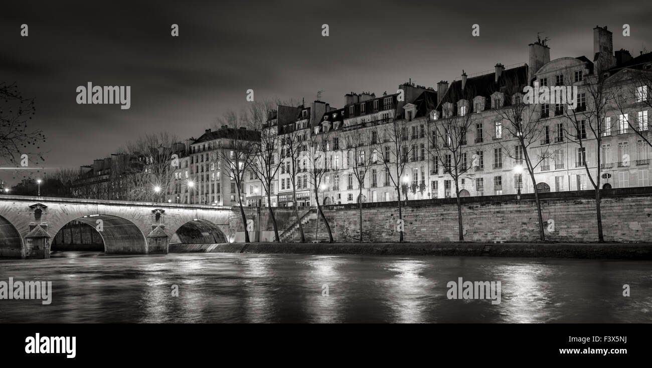 Seine River, Quai de Bourbon on Ile Saint Louis with Pont Marie and evening lights. Row of 19th century buildings, - Stock Image