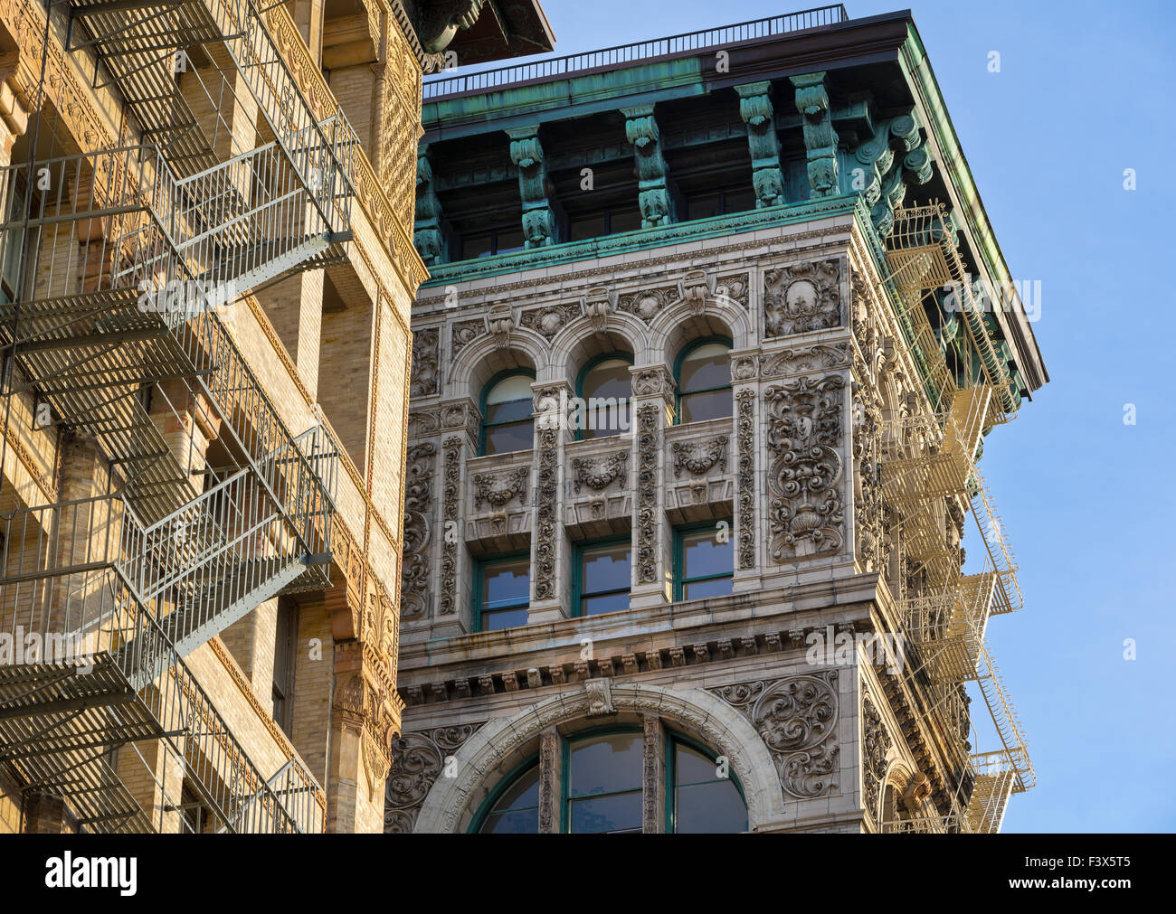 Building facade with terra cotta ornament, copper cornice and fire escapes in Soho, Broome Street, Manhattan, New - Stock Image