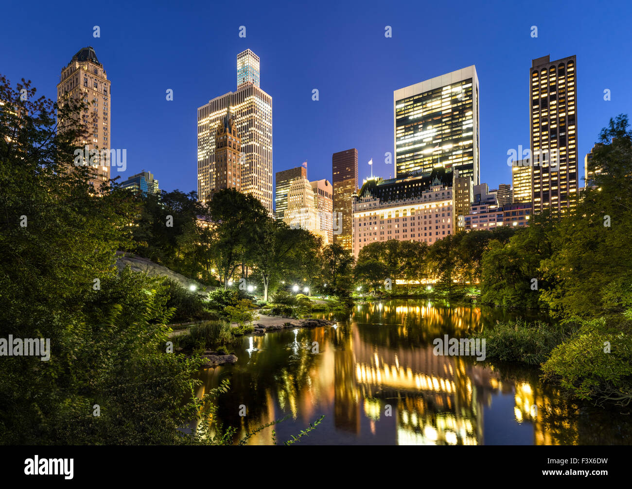 Manhattan skyscrapers illuminated in early evening light. The buildings reflect in the Central Park Pond. New York - Stock Image