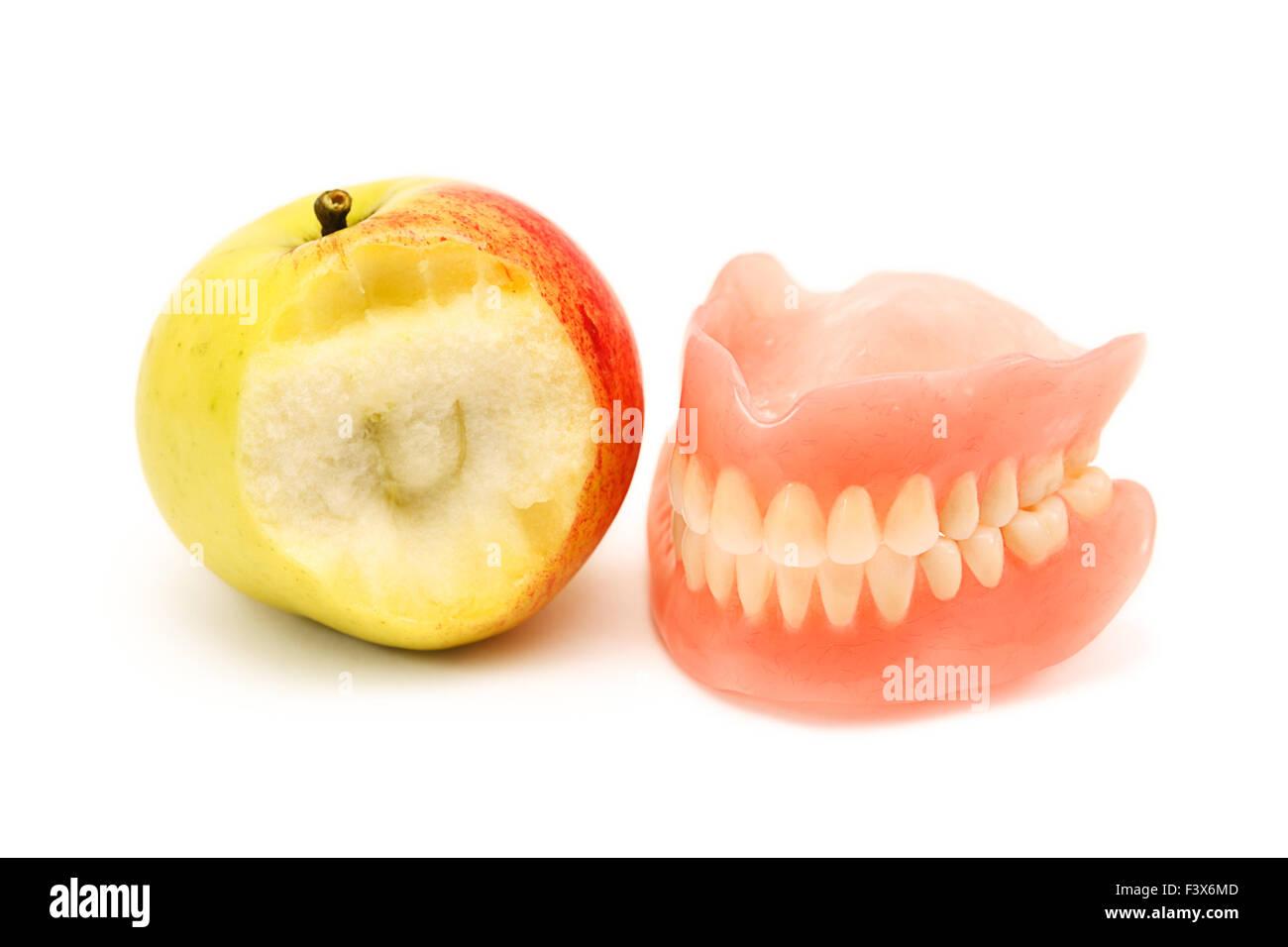 Denture and bitten apple - Stock Image