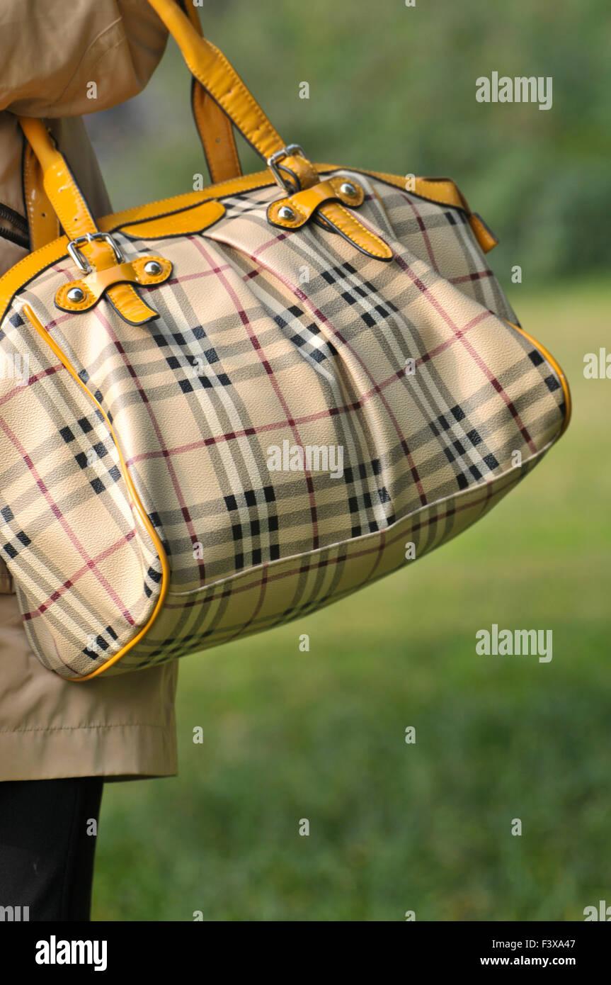 Closeup of brown leather bag handbag in hand of stylish woman fashionable girl on green - Stock Image