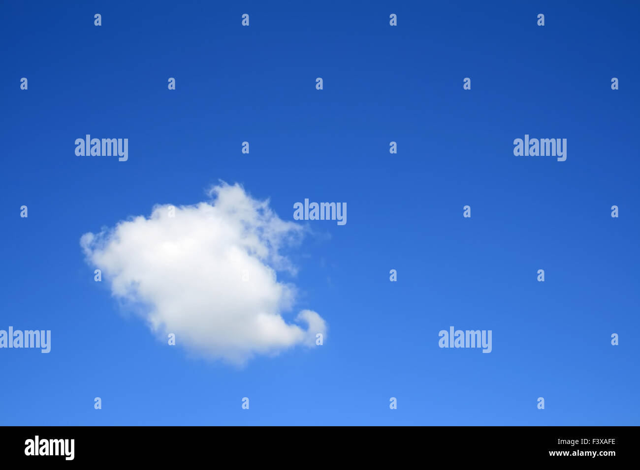 Clear blue sky with one cloud - Stock Image