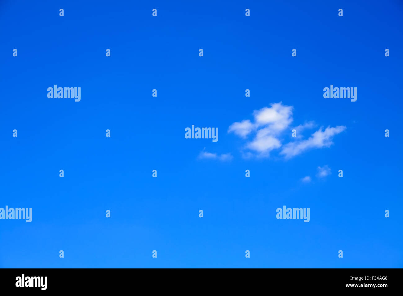 Clear blue sky with one little cloud - Stock Image