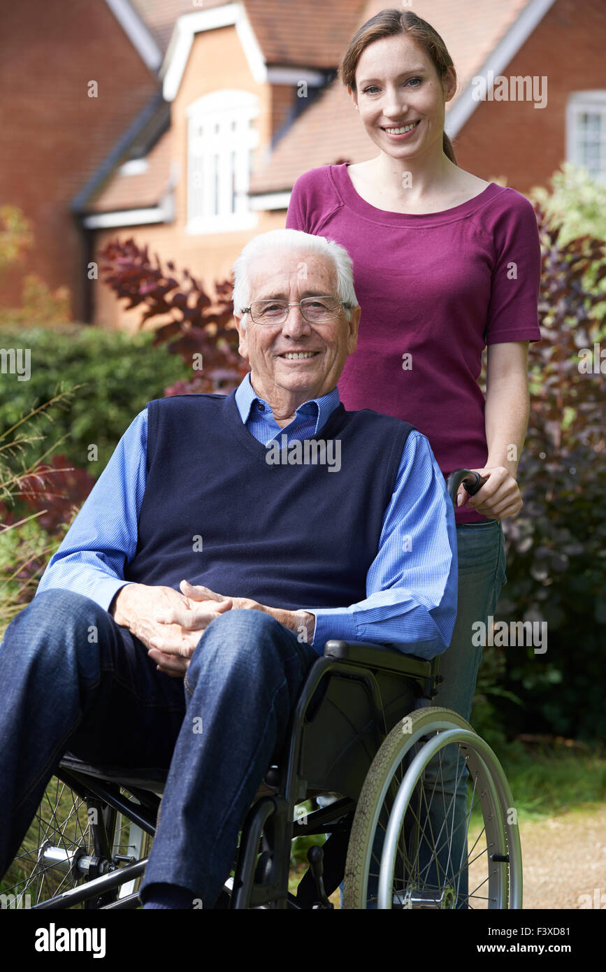 Adult Daughter Pushing Father In Wheelchair Stock Photo
