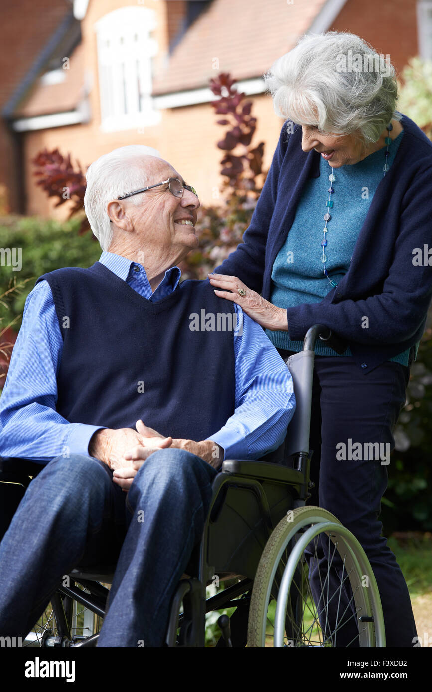 Senior Man In Wheelchair Being Pushed By Wife - Stock Image