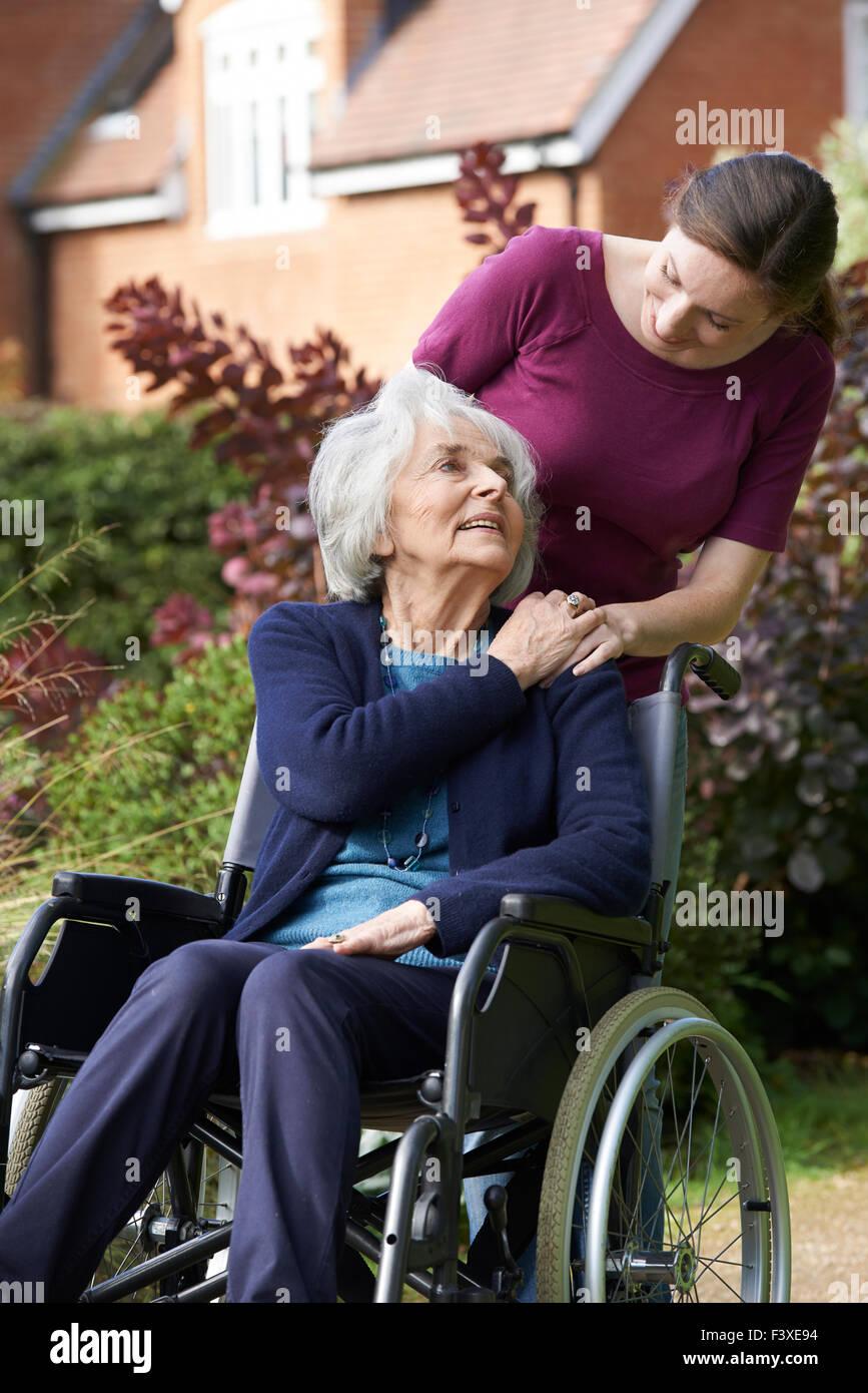 Daughter Pushing Senior Mother In Wheelchair - Stock Image