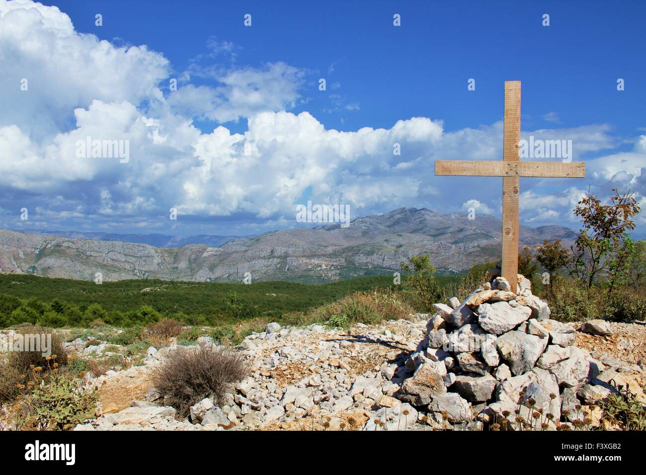 Wooden cross on a grave in the mountains Stock Photo