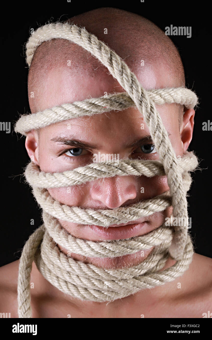 Portrait of a man with rope on his head - Stock Image