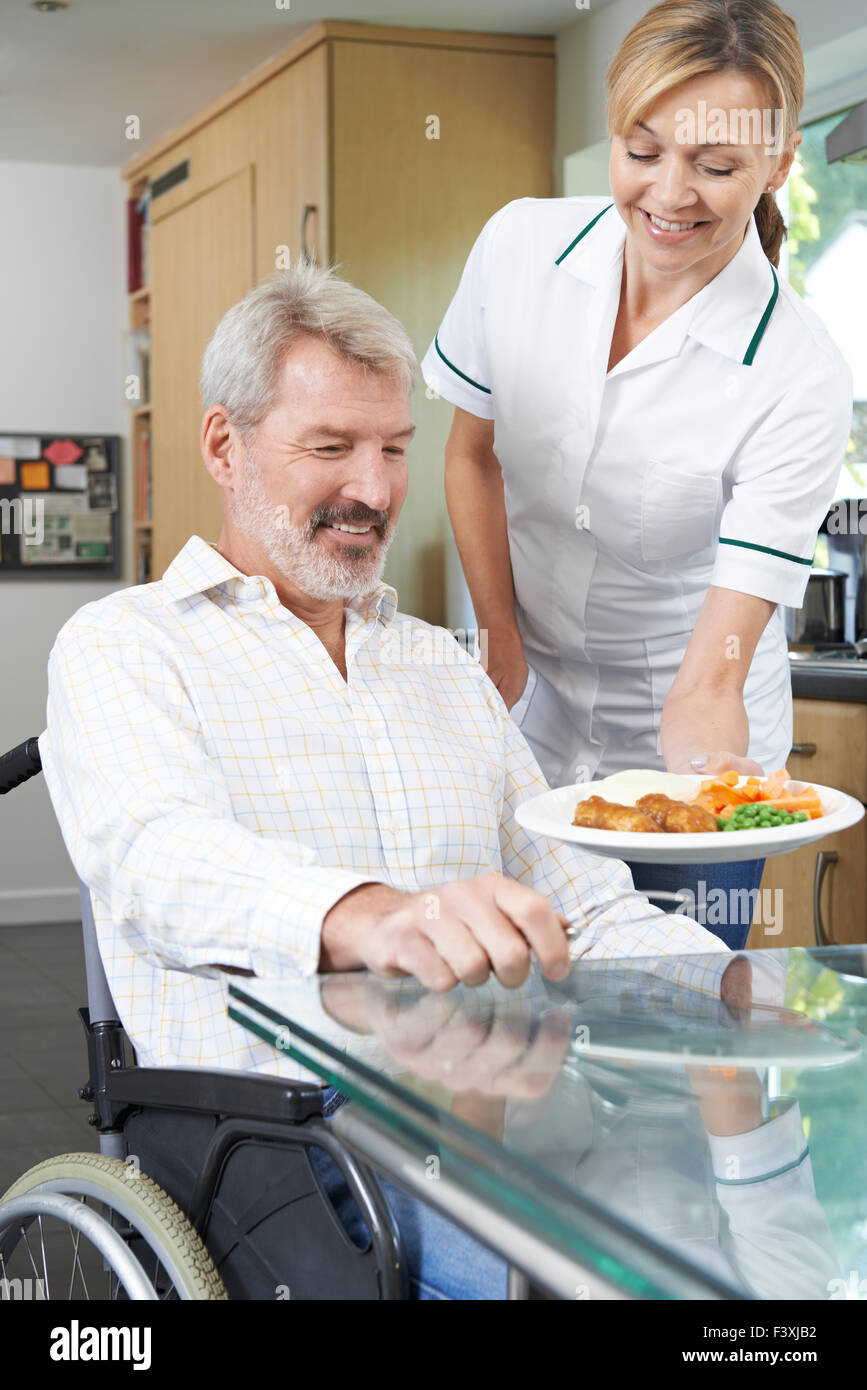 Carer Serving Meal To Man In Wheelchair At Home - Stock Image
